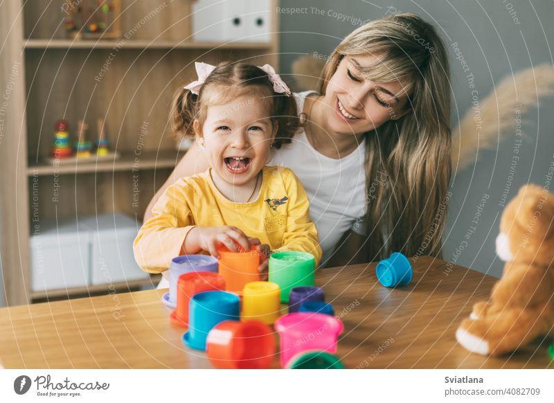 Mama und ein lachendes kleines Mädchen spielen mit bunten Förmchen am Tisch zu Hause. Gemeinsame Zeit, Mutterschaft, Elternschaft Kind heimwärts Spiel Formen