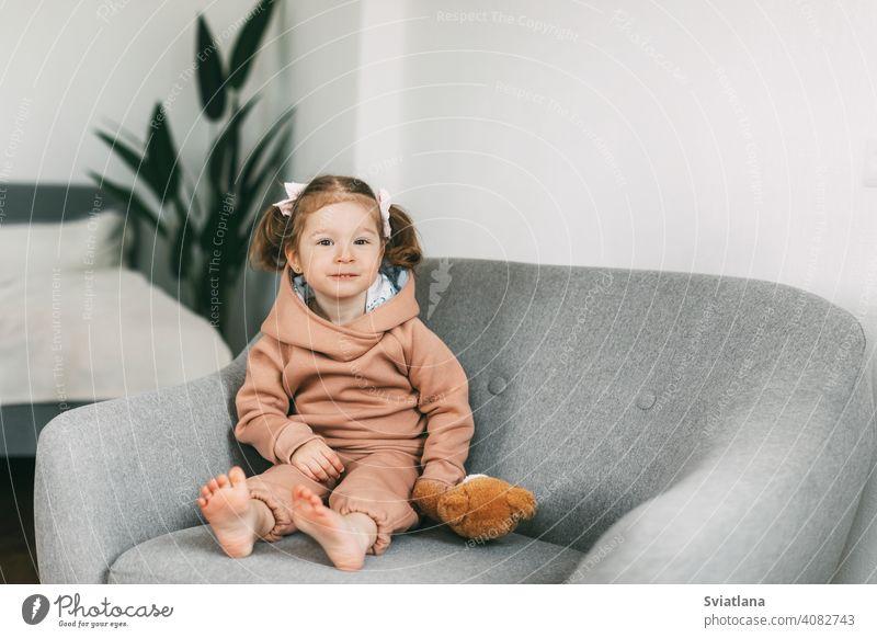 Ein kleines charmantes Mädchen sitzt mit ihrem Spielzeugbären auf einem Stuhl und lächelt wenig Kind niedlich Sitzen Bär Kindheit Teddybär Glück Spaß bezaubernd