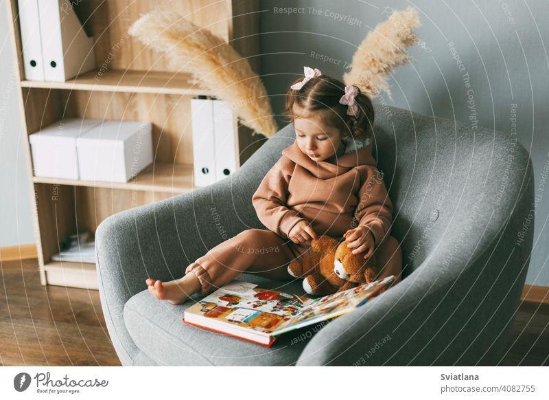 Ein süßes kleines Mädchen blättert durch ein buntes Lehrbuch und sitzt auf einem Stuhl im Zimmer. Entwicklung, Bildung, Kindheit Buch Sitzen Kleinkind wenig