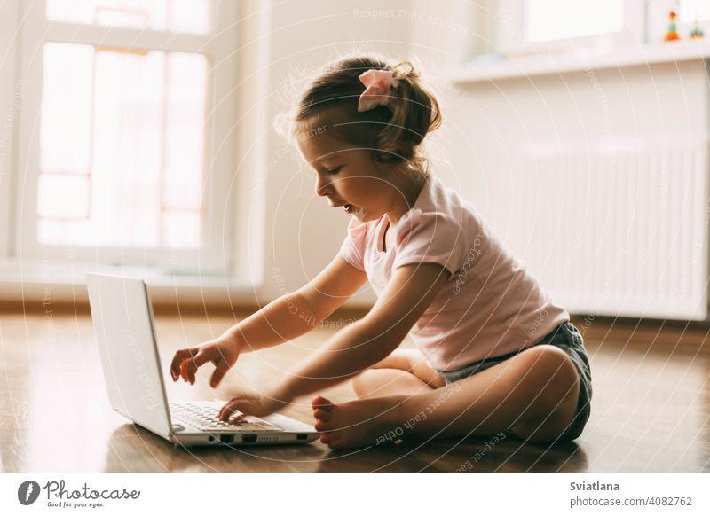 Ein kleines Mädchen spielt oder schaut Cartoons auf einem Laptop und sitzt auf dem Boden in einem Raum. Kindheit, Erholung, Cartoon Zeit wenig Computer Blick
