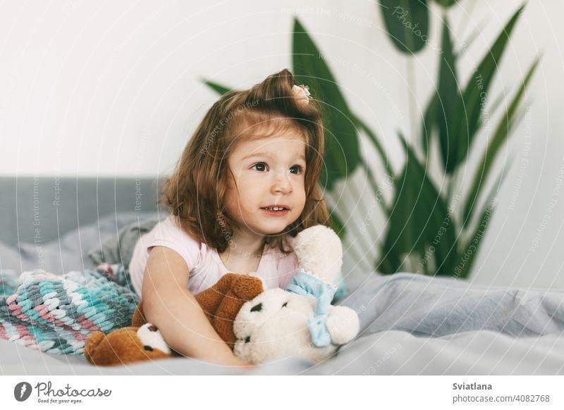 Porträt eines reizenden kleinen Mädchens, das mit seinem Teddybär auf einem Bett liegt wenig Glück Decke niedlich Morgen Pyjamas unten lacht Schlafzimmer