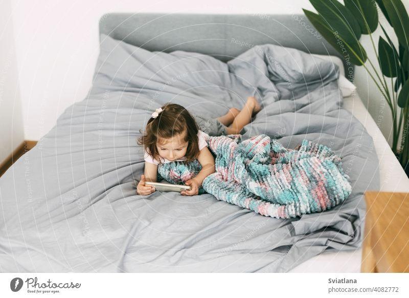 Ein kleines Mädchen schaut Cartoons auf ihrem Telefon oder spielt auf dem Bett, bevor es ins Bett geht. Ansicht von oben Smartphone Kind Mobile heimwärts