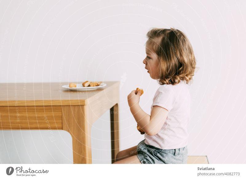 Ein kleines Mädchen sitzt an einem Tisch und isst Kekse wenig Kind Glück Ernährung Lebensmittel jung Kindheit niedlich Küche Gesicht Menschen essen Gesundheit