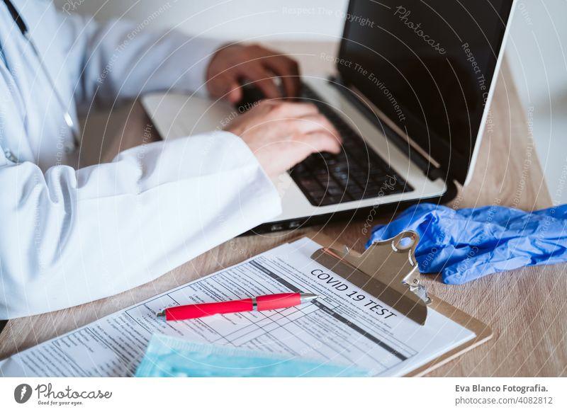 Arzt Mann arbeitet am Laptop. Corona-Virus-Test auf dem Tisch. Covid-19 Konzept Prüfung covid-19 Schutzhandschuhe Schutzmaske Technik & Technologie Analyse