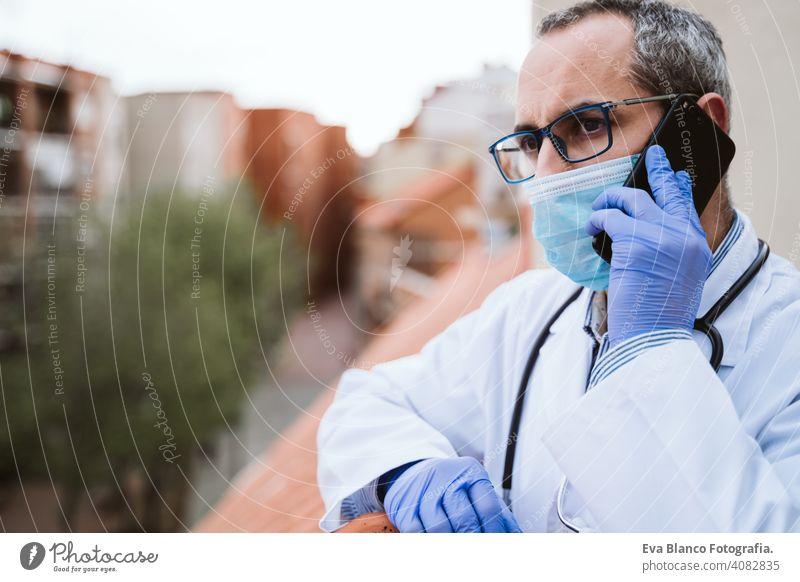Arzt Mann eine Pause machen, mit Handy. Das Tragen von Schutzhandschuhen, Maske und Stethoskop. coronavirus covid-19 Konzept Corna-Virus Schutzmaske Porträt