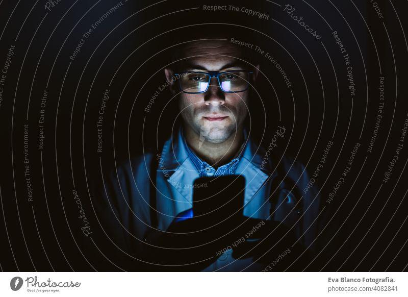 Arzt Mann im Haus, mit Handy. Trägt Schutzhandschuhe, Maske und Stethoskop. coronavirus covid-19 konzept im Innenbereich benutzend Internet tecgnology
