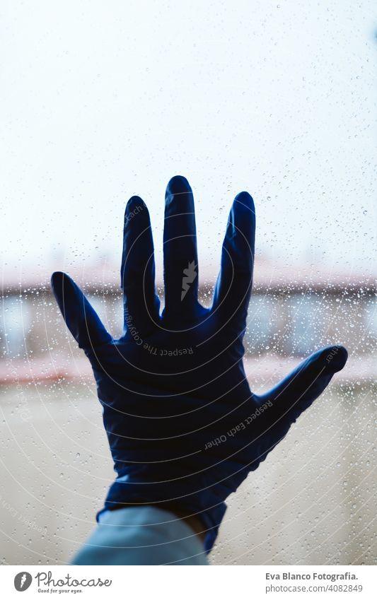 Hand eines Arztes an einem Fenster, regnerischer Tag. Coronavirus covid-19 Konzept professionell Corona-Virus Krankenhaus arbeiten Infektion Handschuh tragend