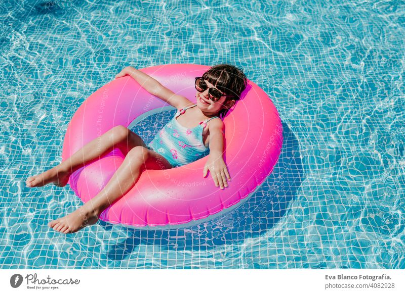 schönes Kind Mädchen schwimmt auf rosa Donuts in einem Pool. Tragen Sie eine Sonnenbrille und lächelnd. Spaß und Sommer Lebensstil Aktivität Schönheit im Freien