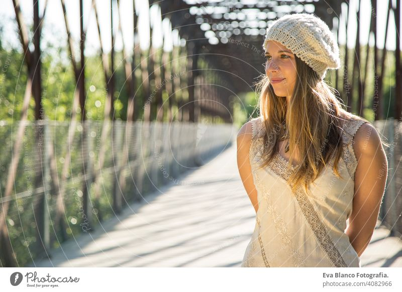 Porträt einer jungen Frau bei Sonnenuntergang im Freien Glück blond Hut blaue Augen Brücke Sommer sonnig Behaarung Fröhlichkeit Lifestyle Gesicht schön Spaß