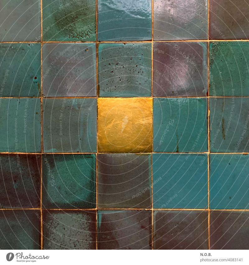 Eine goldene Kachel zwischen andersfarbigen Kacheln Fliesen u. Kacheln blau Wand Quadrat Goldene kachel Menschenleer Fugen einzigartig Einzigartigkeit besonders