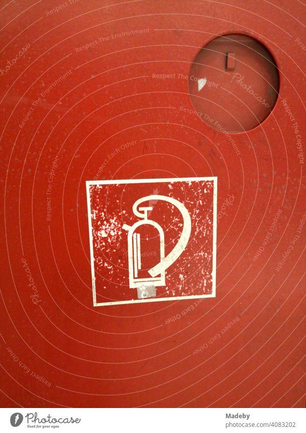 Symbol eines Feuerlöscher in Weiß auf dem roten feuerfesten Metallschrank in der U-Bahn Station Bochenheimer Warte im Stadtteil Bockenheim in Frankfurt am Main