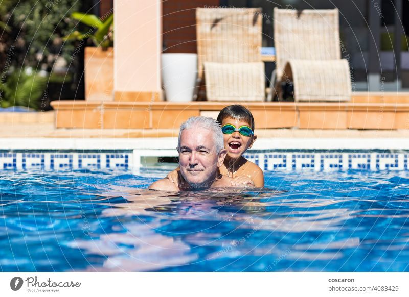 Opa und Enkel spielen auf einem Schwimmbad im Sommer aktiv Aktivität Erwachsener Baby Junge Kaukasier heiter Kind Kindheit älter genießen Genuss Familie Vater