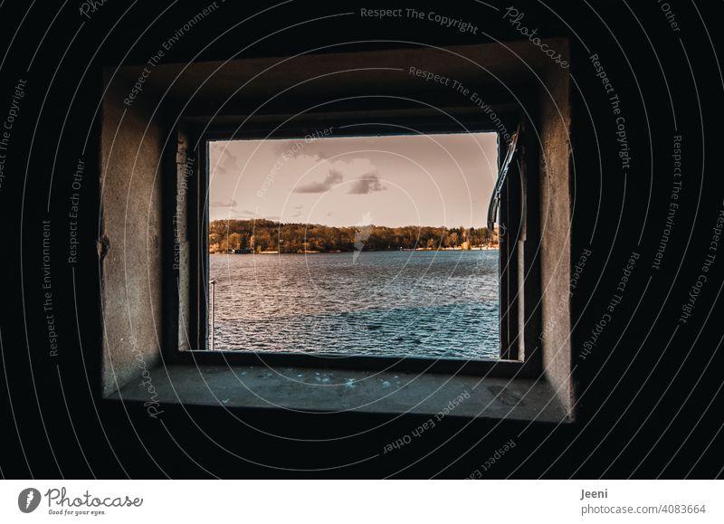 Einen Moment den Ausblick genießen | Blick aus einem kleinen Fenster des alten Hafenspeichers auf das Wasser ausblick Loch herausschauen ausblick genießen
