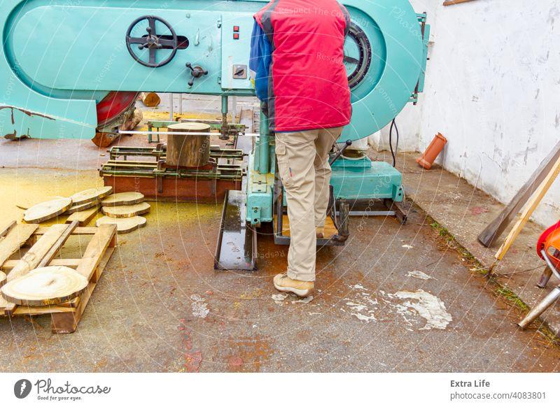 Gestapelte Holzringe auf einer Palette nach dem Schneiden auf der Bandsäge, der Arbeiter schneidet und stapelt Klinge Zimmerer Schreinerei gehackt kreisrund