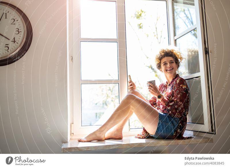 Junge Frau sitzt auf dem Fensterbrett und verwendet Smartphone Glück Lächeln heiter Appartement Freizeit Schlafzimmer Haus heimwärts Raum allein eine Menschen