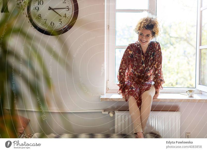 Entspannte Frau zu Hause sitzen am Fenster Glück Lächeln heiter Appartement Freizeit Schlafzimmer heimwärts Raum allein eine Menschen Kaukasier Erwachsener