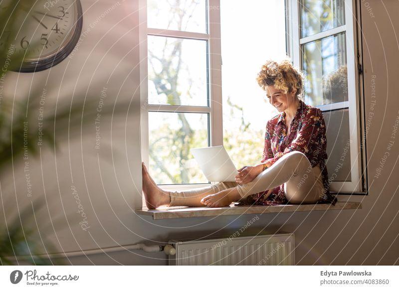 Junge Frau sitzt auf der Fensterbank und verwendet Laptop Glück Lächeln heiter Appartement Freizeit Schlafzimmer Haus heimwärts Raum allein eine Menschen