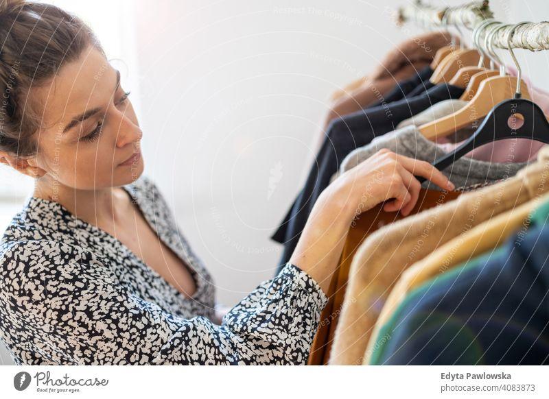 Junge Frau beim Einkaufen in einer Kleiderboutique Mode Bekleidung Kleidung modisch Ablage auserwählend Einzelhandel Laden Werkstatt Sale Kleiderbügel Kunde