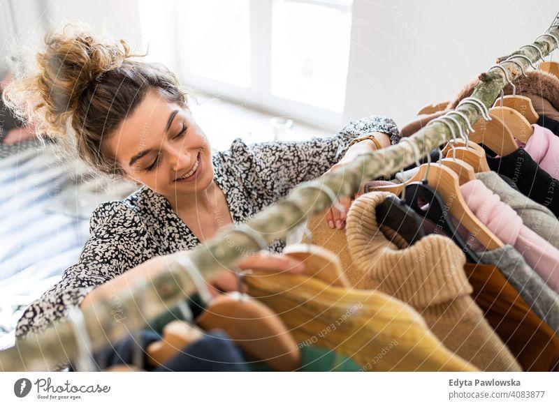 Junge Frau wählt Kleidung Glück Lächeln heiter Appartement Freizeit Schlafzimmer Haus heimwärts Raum allein eine Menschen Kaukasier Erwachsener im Innenbereich