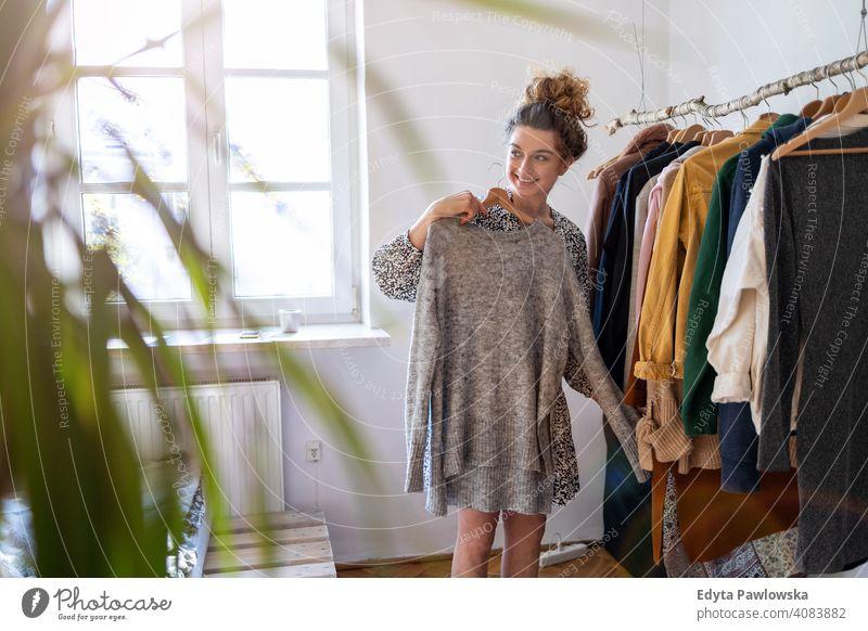 Junge Frau wählt Kleidung Mode Bekleidung modisch Ablage auserwählend Einzelhandel Laden Werkstatt Sale Kleiderbügel Kunde Stil Käufer konsumgeil Kleiderschrank