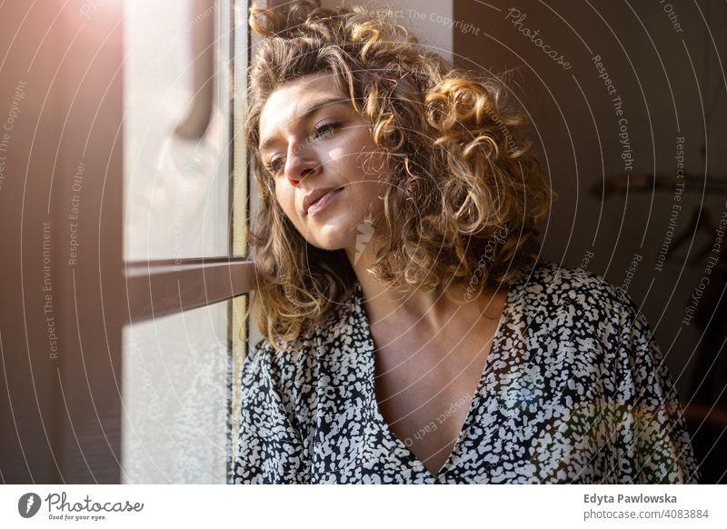 Junge Frau schaut aus dem Fenster Sperrung zu Hause bleiben COVID Coronavirus Pandemie Quarantäne soziale Distanzierung Krankheit Seuche Infektion Virus