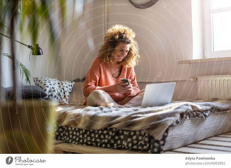 Junge Frau arbeitet im Bett zu Hause mit Laptop Bildung Lernen studierend Hausaufgabe Buch E-Learning Technik & Technologie Computer arbeiten Internet online