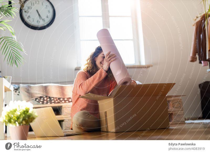 Frau beim Auspacken einer Kiste mit Trainingsgeräten zu Hause Gerät Fitness Übung Trainingsmatte Fitnessstudio Kasten Kollo Verpackung kaufen Verkauf online