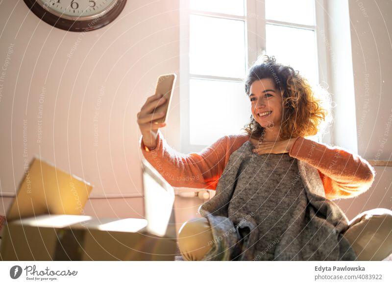 Frau, die ein Selfie macht, während sie Kleidung zu Hause anprobiert Mode Bekleidung Kasten Kollo Auspacken Verpackung kaufen online Internet Paket Karton