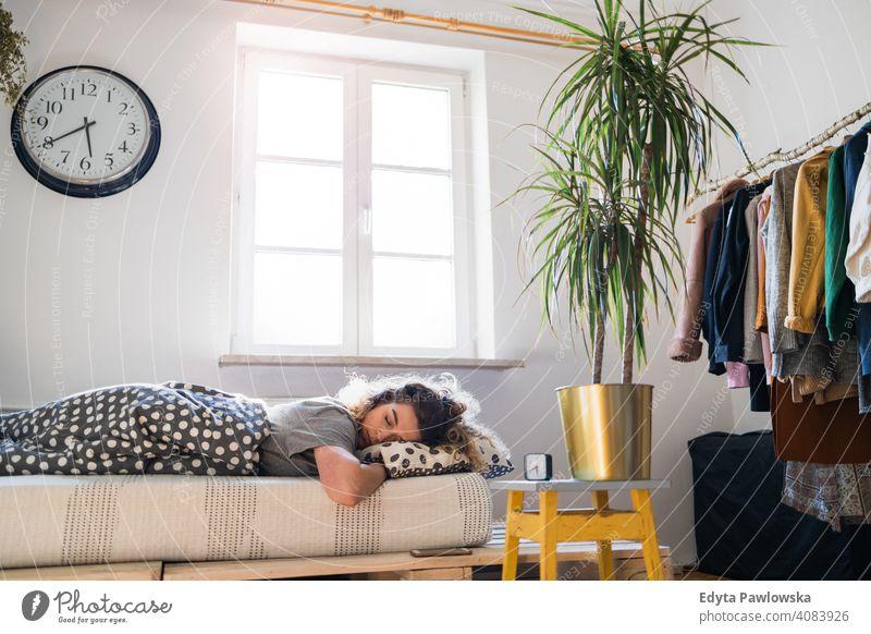 Junge Frau schlafend im Bett Morgen Uhr aussruhen Erholung wach Wecker schläfrig Aufwachen Appartement Freizeit Schlafzimmer Haus heimwärts Raum allein eine