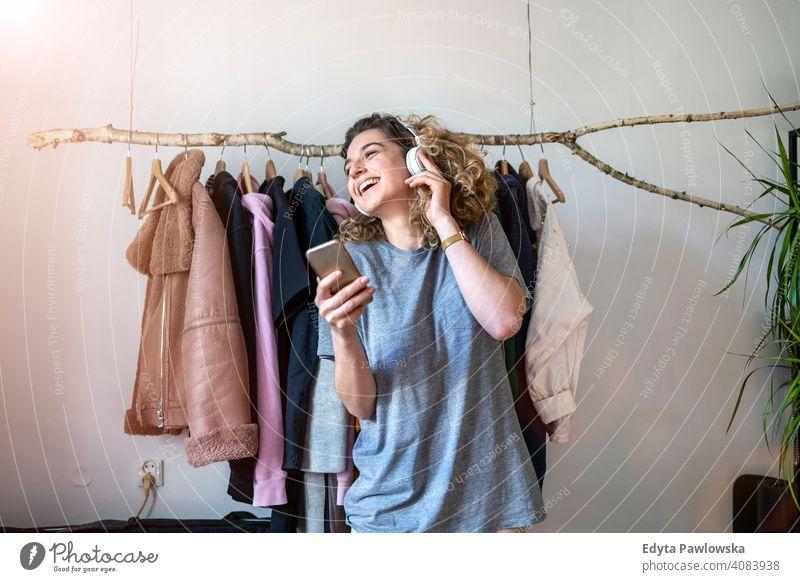 Junge Frau hört Musik in ihrem Schlafzimmer Mode Bekleidung Kleidung modisch Ablage auserwählend Einzelhandel Laden Werkstatt Sale Kleiderbügel Kunde Stil