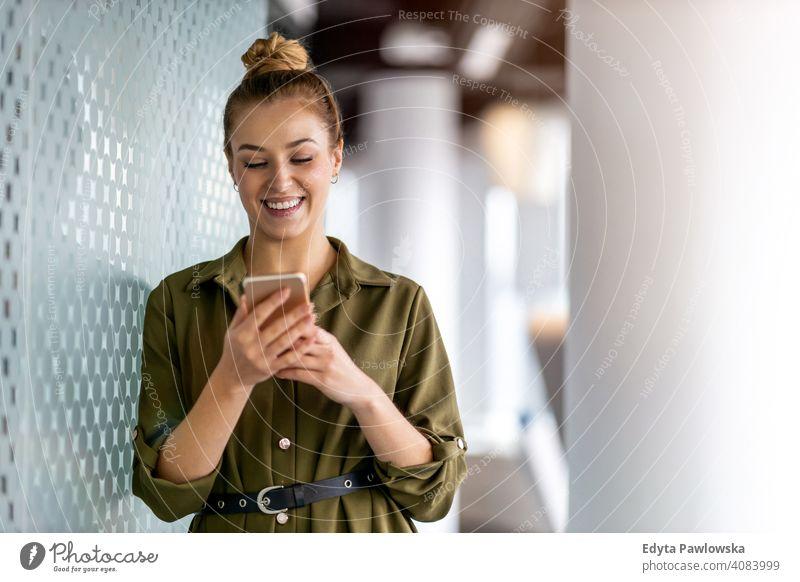 Junge Geschäftsfrau mit Mobiltelefon in ihrem Büro Frau Mädchen Menschen Unternehmer Business gelungen Erfolg professionell jung Erwachsener Lifestyle