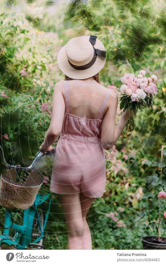 Stilvolles Mädchen in einem Strohhut und einem blassrosa pudrigen Jumpsuit geht mit einem mintfarbenen Fahrrad im Garten eines Landhauses spazieren. Sie hält einen Strauß frischer rosa Pfingstrosen in den Händen. Steht mit dem Rücken zur Kamera