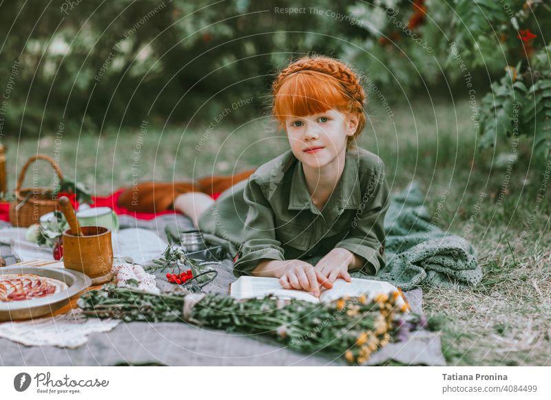 Rothaarige kleine Mädchen lesen Buch bei Retro-Picknick im Freien altehrwürdig retro Frisur Kleid Etage Geschichte lernen positiv Garten hübsch Decke Kleinkind