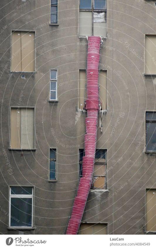 Rote Schuttrutsche vor einer grauen Hausfassade auf einer Baustelle im Prenzlauer Berg rot grau in grau Fassade Fenster Stadt urban Gebäude Gebäudefassade