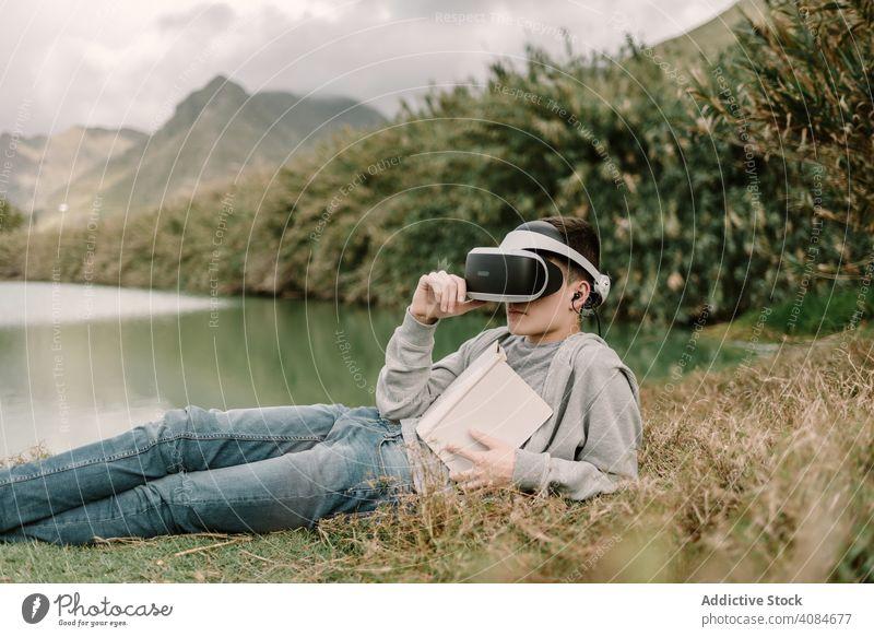 Junger Teenager mit Virtual-Reality-Brille beim Lesen im Freien virtuell Realität lehrreich VR Jugendlicher Natur Headset Technik & Technologie futuristisch 3d