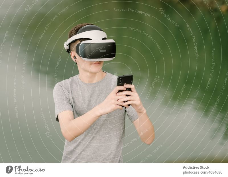 Junger Teenager mit Virtual-Reality-Brille und Smartphone im Freien virtuell Realität VR Jugendlicher Telefon Natur Stehen Headset Technik & Technologie Spiel
