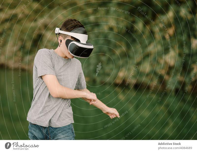 Junger Teenager mit Virtual-Reality-Brille im Freien virtuell Realität VR Jugendlicher Natur Headset Technik & Technologie Spiel futuristisch 3d jung modern