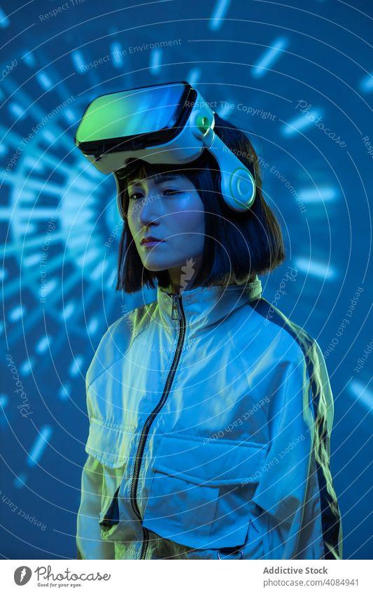 Frau im VR-Headset virtuell Realität Technik & Technologie neonfarbig Licht berührend Gerät digital Innovation jung Person Brille asiatisch modern Entertainment