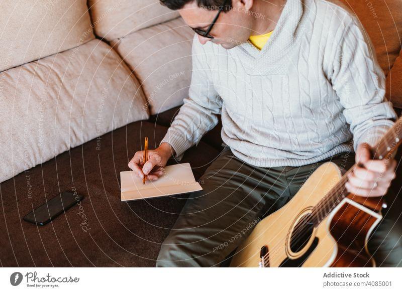 Musiker schreibt in ein Notizbuch Gitarre Notebook schreibend akustisch Schüler Appartement Bleistift heimwärts Mann Hand Raum jung spielen Entertainment Typ