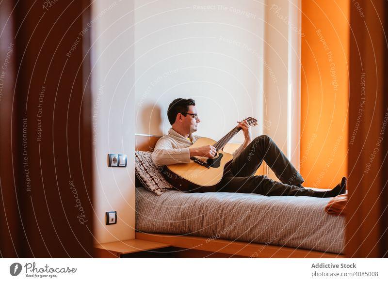 Mann spielt die Gitarre auf dem Bett Spielen Musik Sitzen heimwärts Schlafzimmer Person männlich Instrument Musiker spielen jung Menschen Kaukasier benutzend