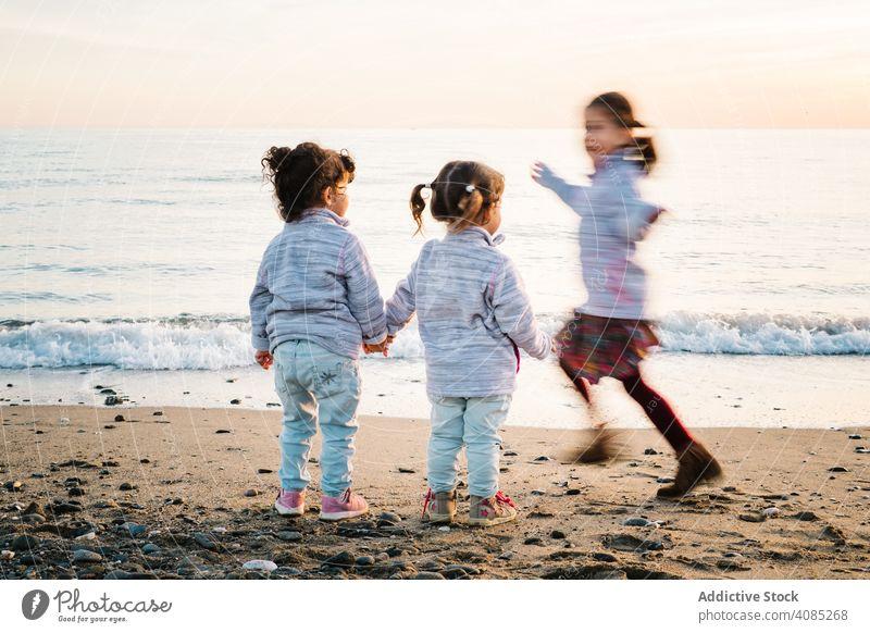 Kinder spielen am Strand rennen Spaß Händchenhalten MEER Schwester Freude Mädchen Freunde Spielen Kindheit drei jung Sand Winter Junge Glück Lifestyle Urlaub