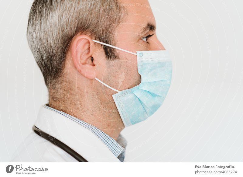 Porträt eines Arztes, der im Haus eine Schutzmaske und Handschuhe trägt. Konzept des Coronavirus Mann professionell Corona-Virus Krankenhaus arbeiten Infektion