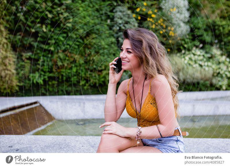 junge blonde schöne Frau auf der Straße im Gespräch am Handy und lächelnd. Lifestyle im Freien. Sommerzeit klug Anruf urban Glück Menschen Lächeln laufen modern