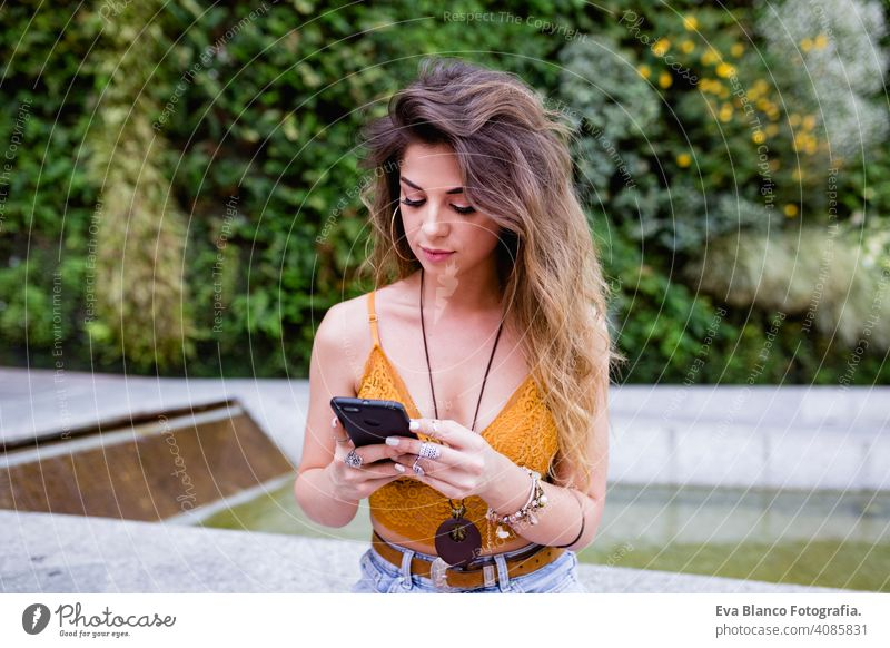 junge blonde schöne Frau auf der Straße mit Handy und lächelnd. Lifestyle im Freien. Sommerzeit, grüner Hintergrund klug urban Glück Menschen Lächeln laufen