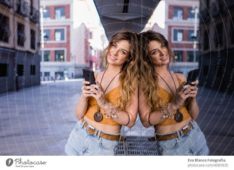 junge blonde schöne Frau auf der Straße mit Handy. Glas-Reflexion. Lifestyle im Freien. Sommerzeit. klug Anruf urban Glück Menschen Lächeln laufen modern spät