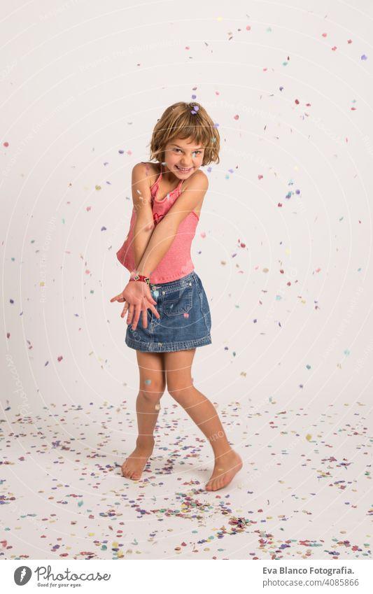 Kind spielt mit Konfetti im Studio. Spaß, Lifestyle, kleines Mädchen Porträt. drinnen, Konfetti auf dem Boden. weißer Hintergrund niedlich Lifestyle-Glück