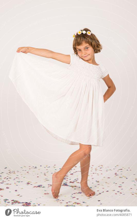 Indoor-Porträt eines Kindes Spaß haben. Konfetti auf dem Boden. weißes Kleid auf kleines Mädchen Porträt. drinnen, Konfetti auf dem Boden. weißer Hintergrund