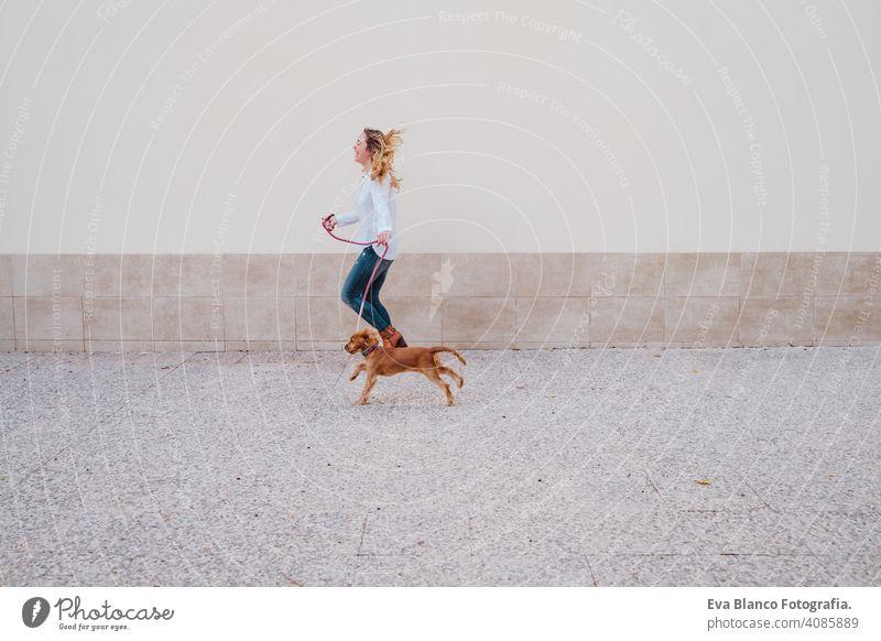 Junge Frau auf der Straße zu Fuß mit ihrem niedlichen Cocker-Hund. Lifestyle im Freien mit Haustieren Freundschaft Großstadt schön laufen Lächeln Tier außerhalb