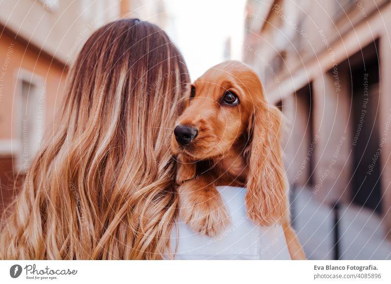 Junge Frau auf der Straße mit ihrem süßen Cocker-Hund auf der Schulter. Lifestyle im Freien mit Haustieren laufen Großstadt urban Reinrassig Kaukasier