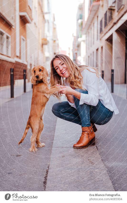 Junge Frau auf der Straße, die ihren süßen Cocker-Hund umarmt. Lifestyle im Freien mit Haustieren laufen Großstadt urban Reinrassig Kaukasier Schürhaken